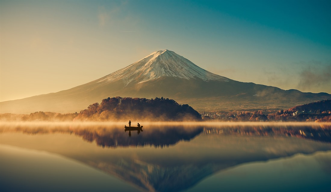 Mount Fuji soars upwards behind Lake Kawaguchiko at sunrise