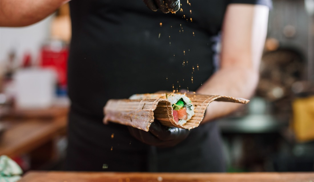 A chef puts the final touches on a traditional sushi roll