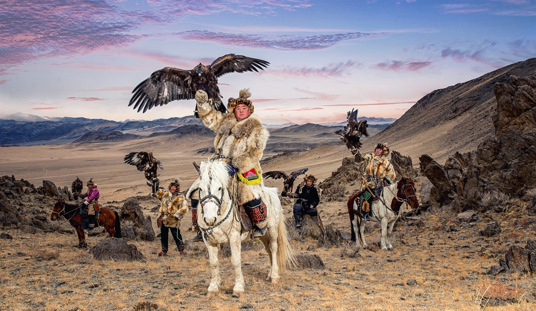 A group of eagle hunters proudly lift their eagles aloft. © Shutterstock/Chanwhit Whanset