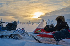 Riding in a snowmobile pulled sled